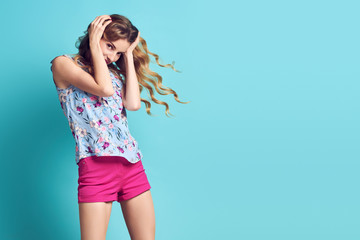 Wall Mural - Portrait Blonde lovable Girl Having Fun in Studio. Young woman laughing dance, Trendy Wavy Hairstyle, Stylish fashion pink shorts. Long-haired Model with Happy positive emotion