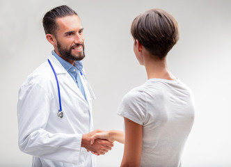 Smiling male doctor shaking hands with a patient