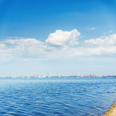 big river and clouds in blue sky. industrial horizon with shipbuilding and storage boxes
