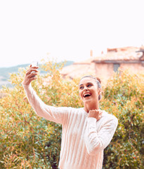 Beautiful young woman in white sweater and underwear, taking selfie, standing on balcony. Tuscany, Italy. Small depth of field.
