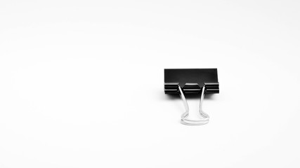 Black paper clip isolated on white background.