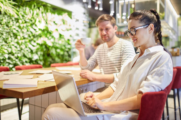 Stylish woman using laptop while sitting at table with man having coffee and working together in light office
