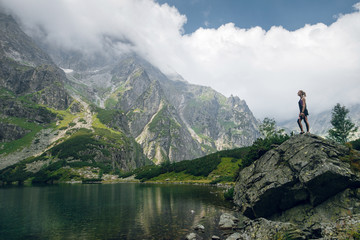 Young blonde sporty woman in sportswear standing on the big rock on the rocky shore and admiring beautiful view of green hills and mountains on Morskie Oko lake, High Tatras, Zakopane, Poland.