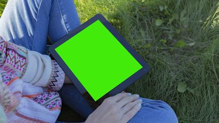 Woman relaxing reading on the tablet computer with pre-keyed green screen