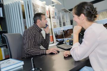Salesman on telephone while customer waits