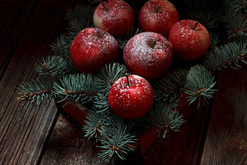 Christmas composition with snowy red apples and green fir-tree branches on rustic wooden background, top view, close up