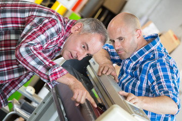 male technicians repairing digital photocopier machine