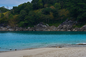 Tropical white sandy beach with rocky mountains and clear water of Indian ocean. View of turquoise bay with rocks  with lush tropical forest. Clear water of the lagoon. Turquoise water background.