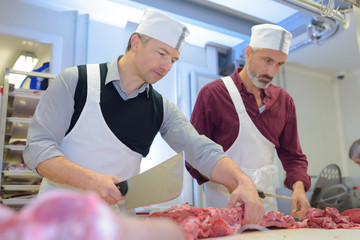 butchers cutting the fresh meat in ham and pork factory