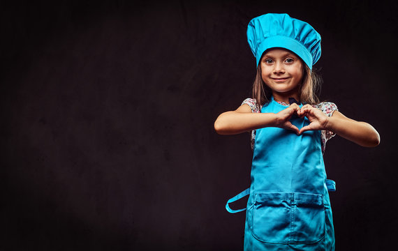 Happy little girl dressed in blue cook uniform shows love gesture. Isolated on a dark textured background.