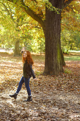 Young smiling woman walking in park on autumn day
