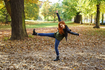 Carefree young redhead woman in a park