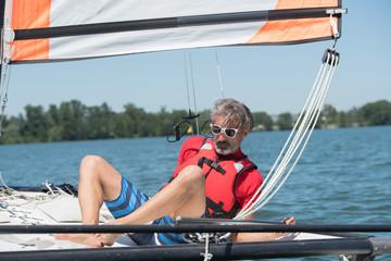 man sailing and dreams on river at summer day