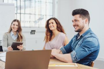 drei kollegen sitzen in einer besprechung im büro
