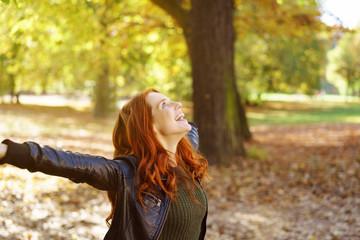 lachende junge frau mit roten haaren breitet ihre arme aus  während eines spaziergangs im wald