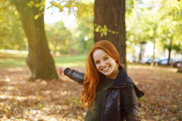 Pretty woman pointing to a colorful autumn park