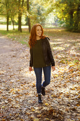 Red-haired smiling woman walking in park