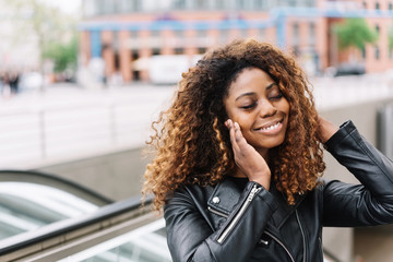 Smiling black woman listening music on earphones