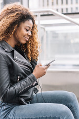 Young black woman listening music on mobile phone
