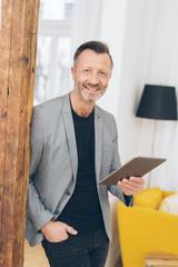 lächelnder mann steht in der wohnung und hält ein tablet in der hand