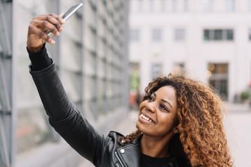 lachende frau macht ein selfie in der stadt