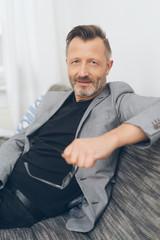 älterer mann mit jacket sitzt auf dem sofa