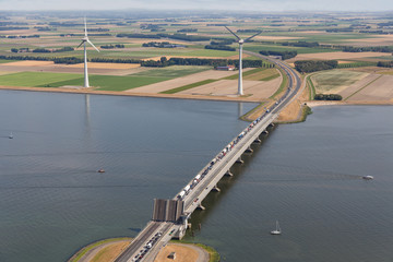Aerial view Dutch agricultural landscape with open bridge and wind turbines along the coast
