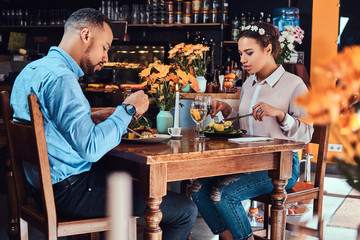 Beautiful African-American couple in love having a great time together at their dating, an attractive couple enjoying each other, eating in restaurant.