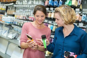 two women choosing paint color in tube in art shop