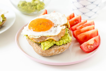 Breakfast sandwich with avocado, ham and eggs, served with fresh tomatoes and a cup of tea on white background.