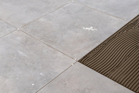 Floor tiles installation. Home improvement, renovation, ceramic tile floor adhesive,
