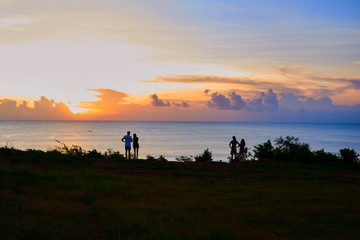 Silhouette couple looking at the beautiful sunset on the top of cliff with the view into oceane. Evening sea landscape with with warm sunlight. Young couple in love enjoy time together during sunset.