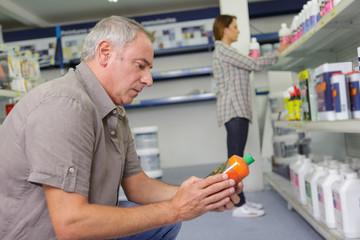 man choosing household chemicals in supermarket