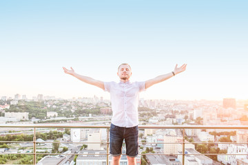 Man's portrait on a high rise building balcony overlooking city with hands rised up to sky, feeling and celebrating freedom, victory, sucsess. Expressing his joy of life. Positive emotion. Copy space.