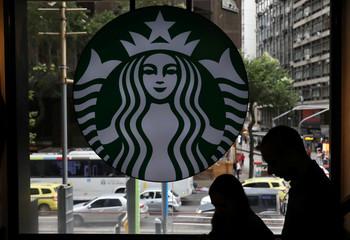 Customers pass by the logo of an American coffee company Starbucks inside a coffee shop in Rio de Janeiro