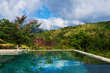 Summer holiday and travel concept. Luxury villa, infinity pool overlooking view mountains and blue sky on the background. Reflection of tropical  trees, white cloud and blue sky on the swimming pool.