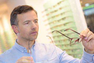 portrait of handsome mature man trying new glasses at optician