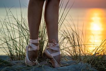 junge Ballerina steht mit Spitzenschuhen im Sand mit Dünengras und einem perfekten Sonnenuntergang über dem Meer im Hintergrund