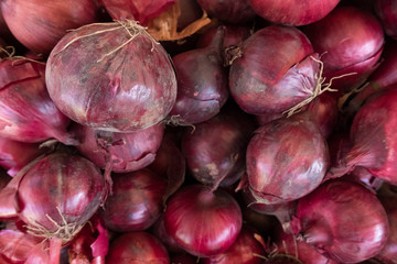 Fresh red onion stand at a street organic food market.