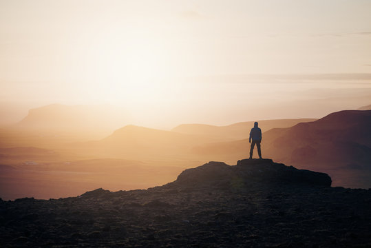 Tourist at sunrise in the mountains