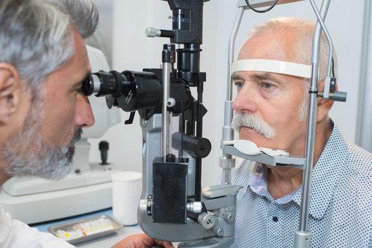 senior taking an eye test examination at opticians