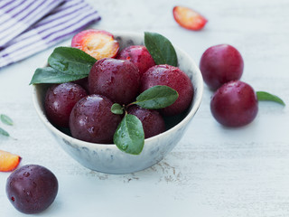 Fresh plums with leaves in a bowl on white rustic wooden table background.