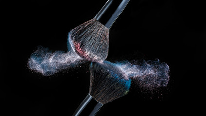 Make up brush with powder splashes on black background
