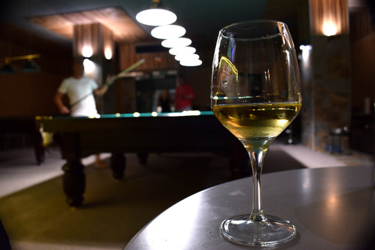 A glass of white wine on a table with billard table on a background