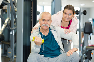 female trainer assisting senior man in lifting dumbbells at gym