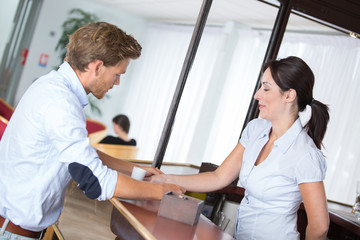 businessman interacting with pretty receptionist at the hotel
