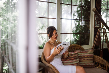 Gorgeous woman reading a book in garden sunroom or conservatory.