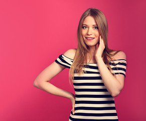Beautiful excited blond long hairstyle woman in striped dress with hand near the face posing on pink background. Toned closeup portrait