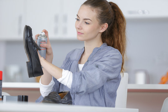young lady spraying product on to shoe