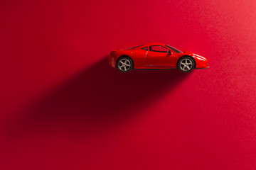 Red toy sports car on a red background.